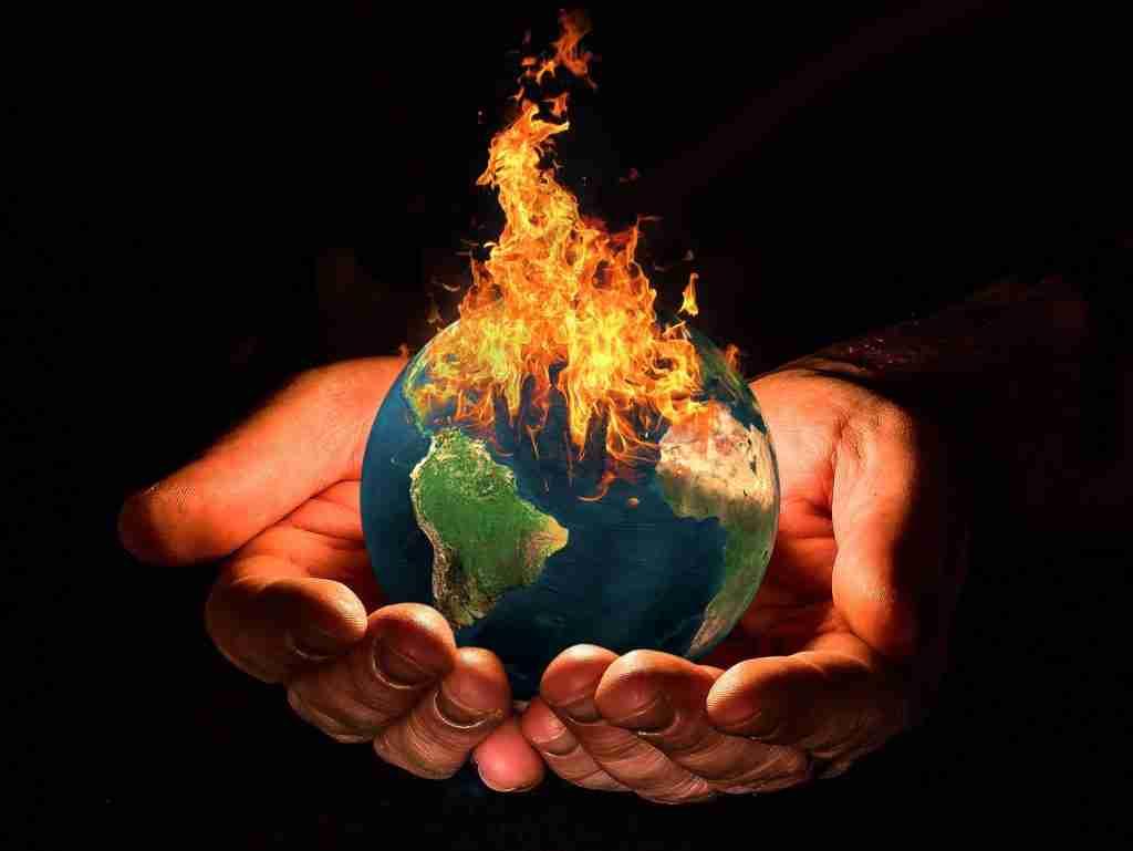 Il Pianeta Terra che prende fuoco nel palmo delle mani di un uomo